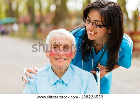 Caring nurse or doctor looking kindly on the elderly patient.