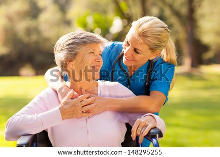 caring nurse with senior patient outdoors