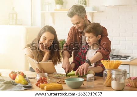 Caring parents and child cooking. father teaching little son use knife. Toothy smiling mother holding cookbook with salad recipe. Home kitchen interior with fresh healthy vegetables food on table