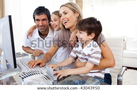 Caring parents teaching their children how to use a computer in the living-room - stock photo
