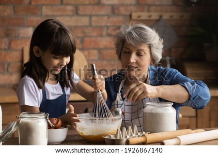 Caring senior Hispanic grandmother and little 8d granddaughter have fun baking cookies at home kitchen together. Loving elderly Latino granny and small grandchild cook tasty sweet breakfast. Foto stock ©