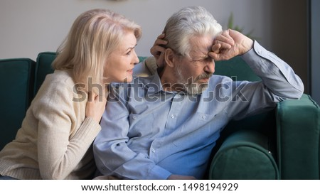 Caring senior wife comfort sad grey-haired elderly husband making peace, reconcile after fight, loving mature woman cuddle help depressed old spouse overcome problem, support him at home