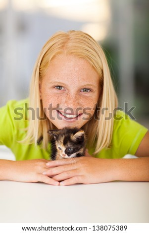 caring teen girl playing with pet kitten at home