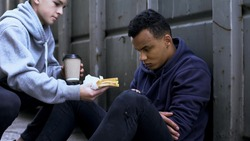 Caring volunteer boy brings dinner to homeless teenager, kind heart, charity