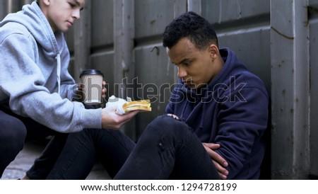 Caring volunteer boy brings dinner to homeless teenager, kind heart, charity