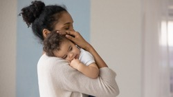 Caring young biracial mother hold lean to chest cute little infant toddler, loving african American mom hug embrace small baby child, relax enjoy tender family moment at home, childcare concept
