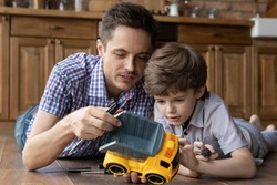 Caring young Caucasian father and little 6s son have fun fixing toy car at home together. Loving dad teach small boy child repair automobile, feel playful relax on family leisure weekend.