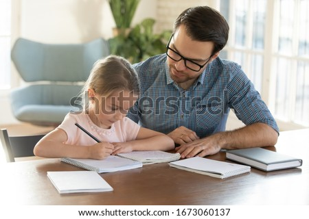 Caring young father helping little daughter with homework. Attentive small schoolgirl studying at home with young daddy. Dad teaching child writing letters in copy book, children education concept.