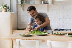 Caring young father show teach little preschooler son chop vegetables prepare healthy diet salad, smiling loving dad learn cooking with small boy child, making lunch on weekend in kitchen together