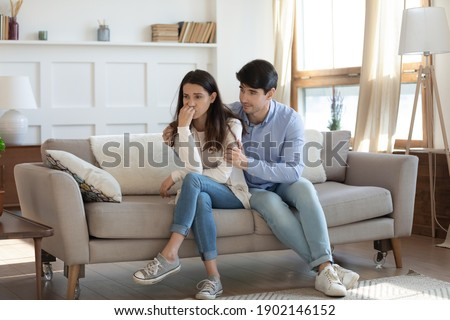 Caring young man hugging woman from back, comforting, apologizing, frustrated wife feeling depressed, thinking about relationship problems, loving husband asking forgiveness after quarrel, conflict Stock photo ©