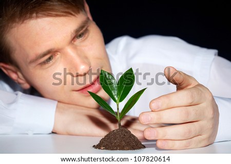 Caring young man protecting green sprout from adverse conditions