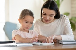 Caring young mom sit at table with small preschooler daughter help with studying, loving mother or nanny teach little girl child, reading together or learning, early development, education concept
