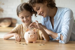 Caring young mother teaching small preschool kid daughter saving money or planning future purchases, putting coins in small piggybank in modern kitchen, financial education for children concept.