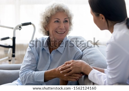 Caring young nurse doctor carer helping holding hands of happy disabled handicapped or injured old adult elder woman having disability health problem sit at home with walking frame walker in hospital