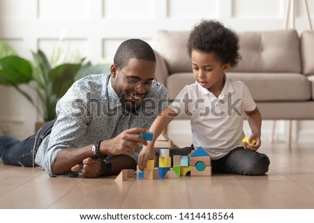 Caring young single black father help cute kid son play on warm floor together, happy african family dad and little child boy having fun building constructor tower from colorful wooden blocks