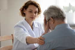 Caring young woman doctor comforting depressed unhealthy mature patient at meeting in hospital, therapist physician gp caregiver touching senior man shoulder, expressing empathy and support