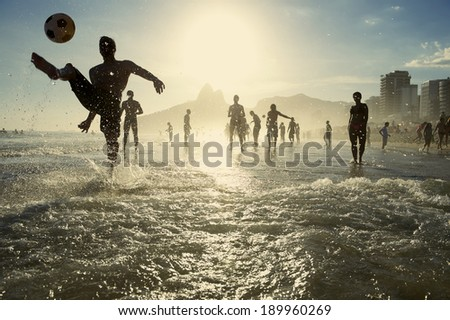 Carioca Brazilians playing altinho beach football in silhouettes kicking soccer balls in the waves of Ipanema Beach Rio de Janeiro Brazil Foto stock ©
