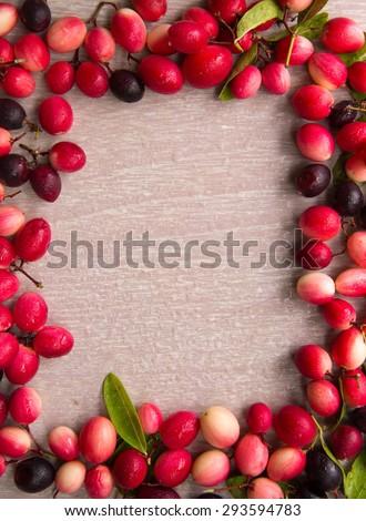 Carissa carandas fruits frame on wooden table
