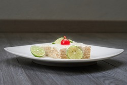 Carlot of lemon lemon foot on a white plate in a gray winegon with a cherry in Albar, made with a bed Circular cookies bathed in a mixture of evaporated milk, condensed milk and lemon
