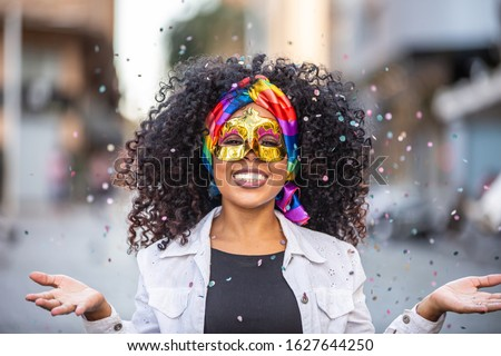 Carnaval party. Brazilian curly hair woman in costume blowing confetti