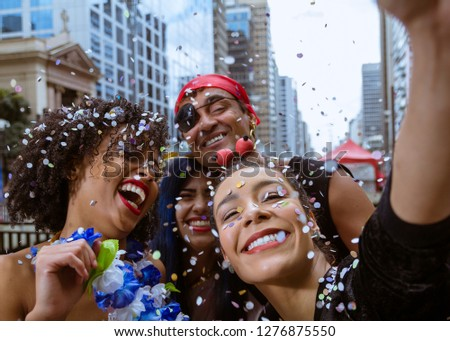 Carnaval party. Group of Brazil people in costume celebrating carnival in the city. Dressed brazilian partygoers having fun in parade festival.