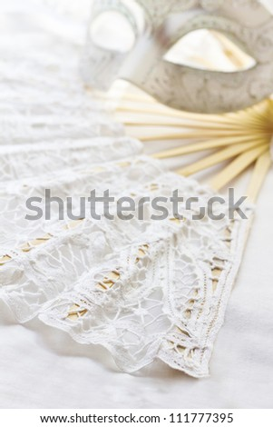 Carnival accessories. White mask for carnival and fan on white background