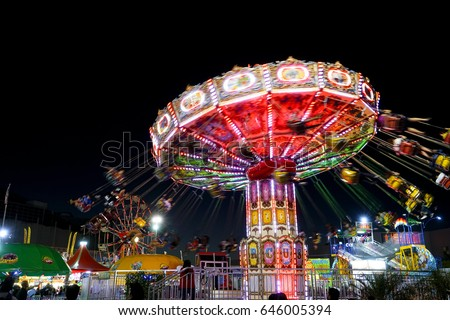 Carnival amusement part with rides that are lit up with colored lights. Blurred fun bright and colorful background. Summer fair at night. Spinning swings with people.