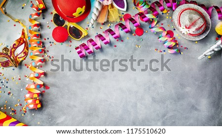 Carnival border of colorful streamers, confetti, hats, masks and sunglasses on grey with copy space for masquerade and party time #1175510620