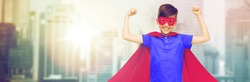 carnival, childhood, power, gesture and people concept - happy boy in red superhero cape and mask showing fists over city background