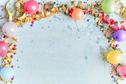 Carnival, festival or birthday balloon background with colorful party streamers, candy and confetti making a border on a blue background with copy space