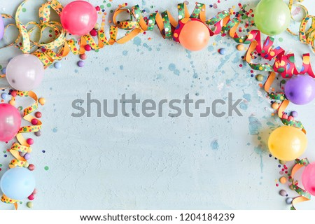 Carnival, festival or birthday balloon background with colorful party streamers, candy and confetti making a border on a blue background with copy space #1204184239