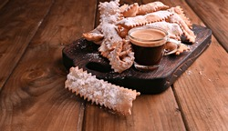 Carnival food TYPICAL and aromatic coffee on a woody background. Sfrappole or chiachiere or angel wings. Traditional sweet crisp pastry deep-fried and sprinkled with powdered sugar.