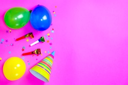 Carnival hats and accessories for birthday celebration lie on bright pink background. Scattered confetti. Copy space for text. Top view. Flat lay. Lay out. Close-up. Holiday.