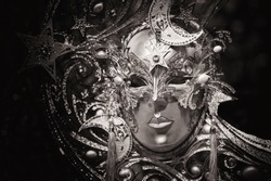 Carnival Mask, nicely decorated with stars and moon, to celebrate venetian carnival with hidden face, black and white photo, Venice, Italy