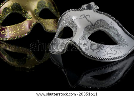 Carnival masks on a black background. The part of masks is reflected by the glass surface