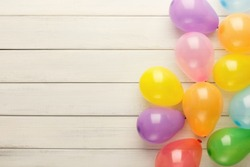 Carnival or party border of colorful balloons, top view. Holiday decoration on rustic wood planks with copy space for greeting, invitation or advertising. Birthday background