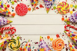 Carnival or party frame of colorful balloons, top view. Holiday decorations, lollipops and confetti on rustic wood planks with copy space for greeting, invitation or advertising. Birthday background