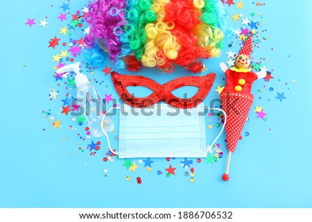 carnival, party and Purim celebration (jewish carnival holiday) over blue background. Coronavirus prevention concept, medical mask