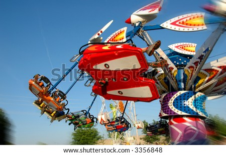 Carnival Ride with motion blur against a colorful blue sky
