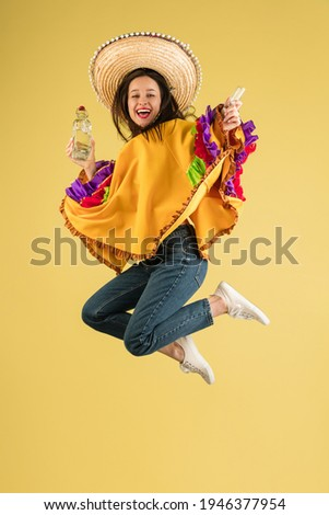 Carnival time. Funny young girl in bright garment, poncho and sombrero isolated on yellow background. Concept of human emotions, facial expressions, national traditions, culture. Cinco de mayo holiday Foto stock ©