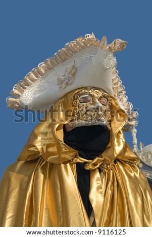 Carnival Venetian disguise with golden mantle on blue sky