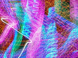 Carnivalesque profusion of light trails in an ornamental garden with festive holiday illumination at night. Long exposure with motion blur. Painting with light.