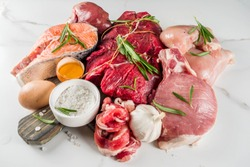 Carnivore diet background. Non vegan protein sources, Different meat food - chicken breast, pork steak, beef tenderloin, eggs, spices for cooking. White marble background copy space