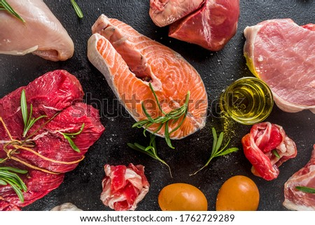 Carnivore diet background. Non vegan protein sources, Different meat food - chicken breast, pork steak, beef tenderloin, eggs, spices for cooking. Black stone concrete background copy space Stock fotó ©