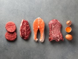 Carnivore or keto diet concept. Raw ingredients for zero carb or low carb diet - burger patties, ribeye, salmon steak, pork, egg on gray stone background.Top view or flat lay.Copy space top and bottom