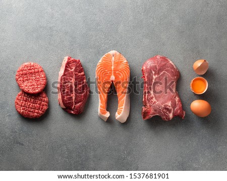 Carnivore or keto diet concept. Raw ingredients for zero carb or low carb diet - burger patties, ribeye, salmon steak, pork, egg on gray stone background.Top view or flat lay.Copy space top and bottom #1537681901