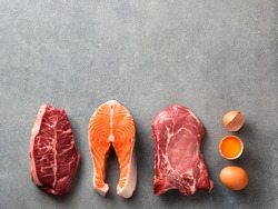 Carnivore or keto diet concept. Raw ingredients for zero carb or low carb diet - rib eye, salmon steak, pork, egg on gray stone background. Top view or flat lay. Copy space top.