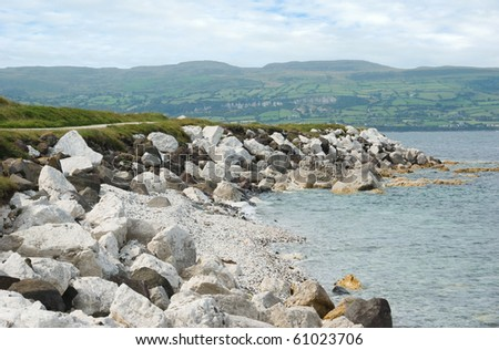 Carnlough Bay on the coast of County Antrim, Northern Ireland, with the Glens of Antrim in the background. The white limestone boulders and pebble beaches are a feature of this popular tourist area.
