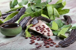 Carob bean(Harnup). Healthy organic sweet carob pods with seeds and leaves on wooden background.