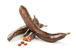 Carob carob fruit and seeds on white background. Isolate. Organic carob beans, a healthy alternative to cocoa. Free space